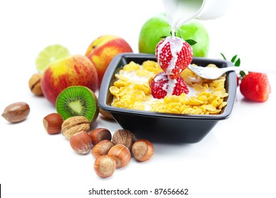 strawberry, peach, nuts,apple, kiwi, milk and flakes in a bowl isolated on white