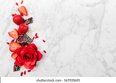 Strawberry, red rose and chocolate on marble background view from above. Flat lay