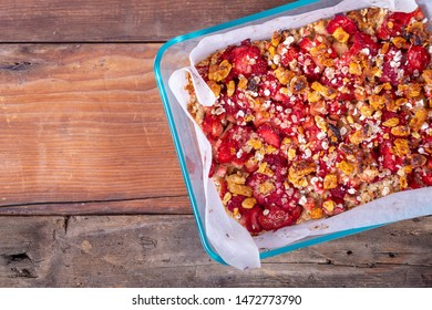 strawberry rhubarb crispy and chewy crumble oatmeal bars baked over wood plank table