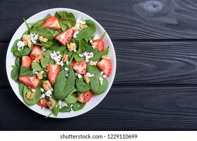 Strawberry salad with spinach , cheese and walnut . Healthy food