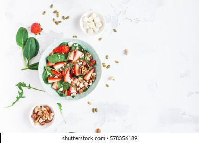 Strawberry salad. Spinach leaves, sliced strawberries, nuts, feta cheese on white background. Healthy food concept. Flat lay, top view.