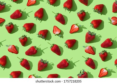 Strawberry seamless pattern, red ripe strawberries on green colored background, top view, flat lay, summer pattern. Trendy wrapping paper, fabric, wallpaper background. Texture
