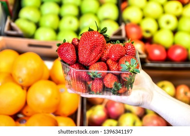 Strawberry in the seller's hand in the grocery market. Stands with fruits on a blurred background.