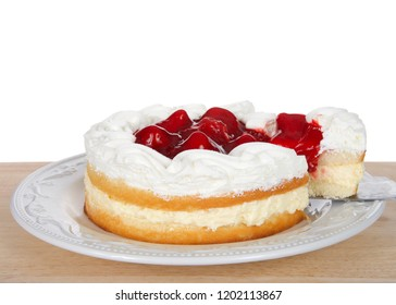 Strawberry short cake with cream filling on white plate, whipped cream and strawberries on top. Slice being pulled out of cake. On wood table isolated white background.