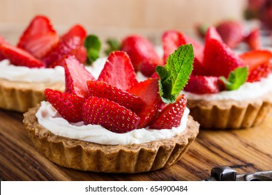 Strawberry shortcake pies on rustic wooden table,  perfect party individual fresh fruit dessert