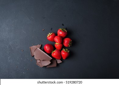 Strawberry with slices of chocolate on a dark background. Copyspase
