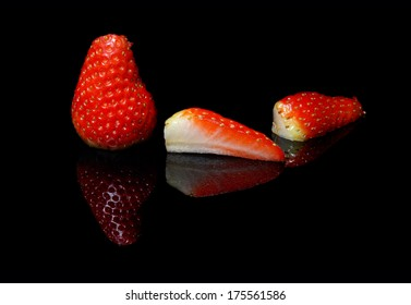 strawberry slices reflected on a black background