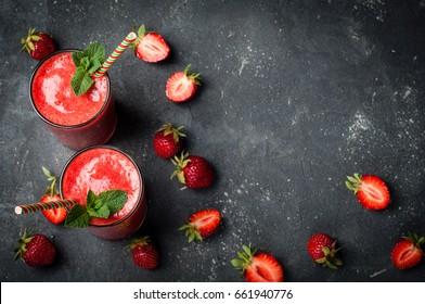 Strawberry smoothie in glass on dark background with copy space. Summer drink cocktail. Healthy eating dieting and breakfast concept. Top view