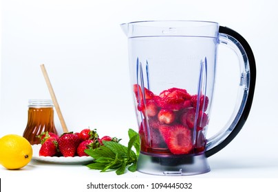 Strawberry smoothie ingredients in a blender isolated
