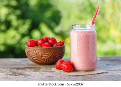 strawberry smoothie in jar and fresh ripe berries in bowl on wooden table with green natural bokeh on the background. Pink milkshake. Healthy summer drink concept