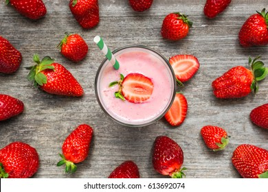 Strawberry smoothie or milkshake in a glass with straw with fresh berries on rustic wooden background. healthy food. top view
