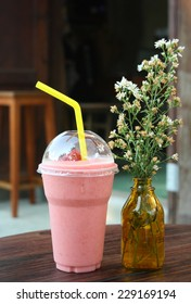 strawberry smoothie in plastic glass on wooden table. feeling fresh with iced drink