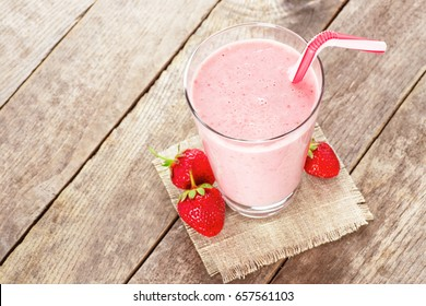 strawberry smoothie with straw in glass on wooden table. Homemade berry cocktail. Top view. Pink milkshake. Healthy drink.