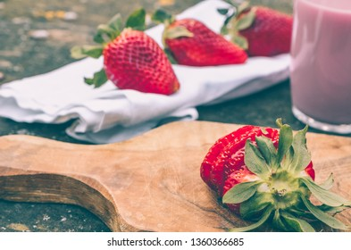 Strawberry smoothie with strawberries around on a rustic wooden table in the countryside