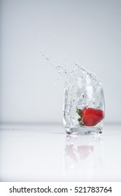strawberry splash into water glass on white background
