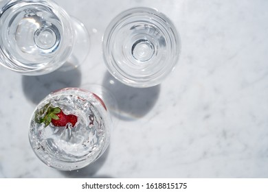 Strawberry Splashing into a Glass of Water from Above on Marble table Top with Copy Space