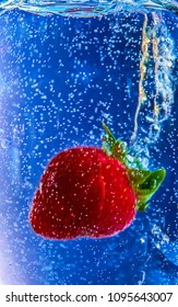 Strawberry splashing into water.