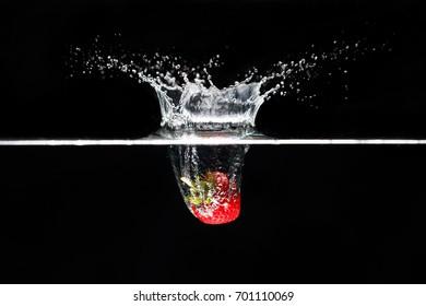 A strawberry splashing into water