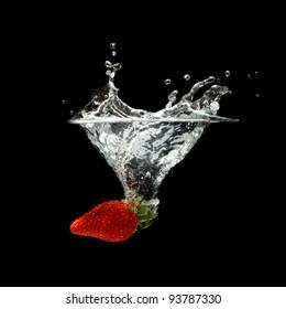 strawberry splashing in water over black background