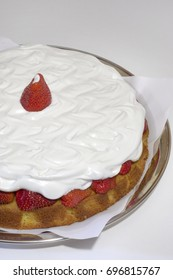 Strawberry sponge cake with whipped cream, with juicy a red berry on top, on a salver