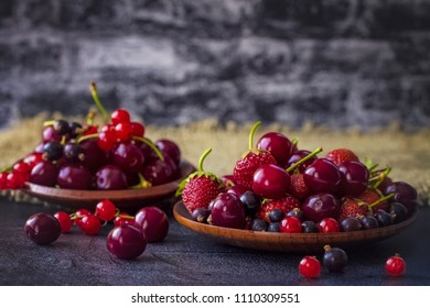 strawberry, sweet cherry, currant in a wooden bowl close-up. garden berries are in a bowl on the table.  background with garden berries. harvest berries.