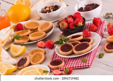 Strawberry tartlets with fresh fruit on white dish.