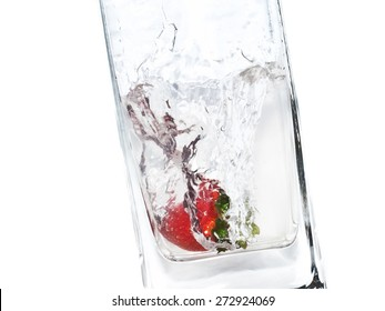 Strawberry in a transparent water splash in a glass as a symbol of romantic summer cocktail party on the beach or healthy lifestyle and good nutrition