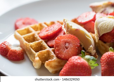 Strawberry waffles. Selective focus closeup of red fruit on authentic homemade sweet pancake waffle. Serving with icecream served on a white plate background.