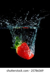 Strawberry in water with bubbles on black ground