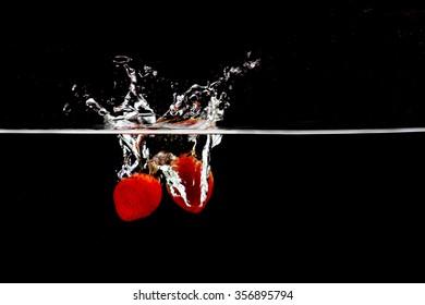 Strawberry in water splash on black background