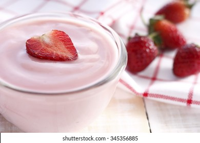 strawberry yogurt with fresh strawberry in heart-like formed on wooden white background.