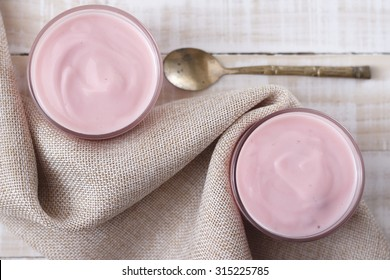 strawberry yogurt in glass cup with vintage spoon on wooden white background.