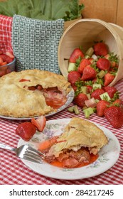 Strawberry-Rhubarb Pie on plate on a country table with strawberries and rhubard and a red and white checkered table cloth