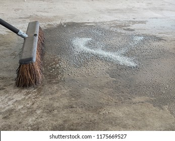 A straw-bristled broom and water cleans up an oil spill in a household garage with oil-absorbing cat box litter granules
