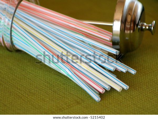 Straws spilling out of a glass container with a chrome lid.