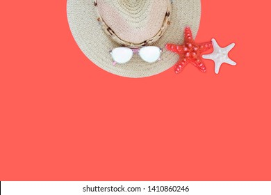 Strawy hat, sunglasses and two sea stars on coral background. Summer beach dress items. Summer, beach concept. Adventure, travle, vacation concept.