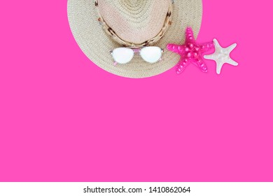 Strawy hat, sunglasses and two sea stars on pink background. Summer beach dress items. Summer, beach concept. Adventure, travle, vacation concept.