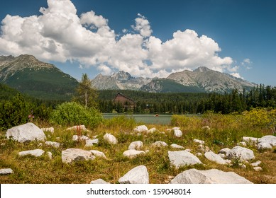 Strbske Pleso in High Tatras Mountains with rocks lying on the grass in foreground