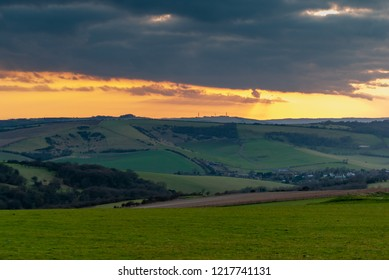 Streak of sunlight between heavy cloud and the rolling hills of the South Downs
