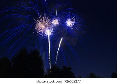 Streaks of blue fireworks light up the night sky