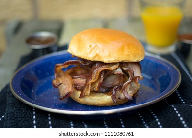 Streaky Bacon in a brioche roll, with orange juice and sauces in the background
