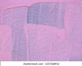 streaky faded pink paint on a wall with drips and brush marks with the original blue color showing underneath
