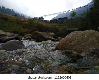 A stream with big stones close by the vintage local houses in mountains.