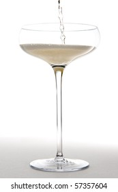 A stream of champagne fills up a saucer stlye champage glass.  Studio isolated on a white background.