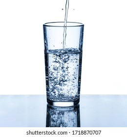 A stream of clean drinking water is poured into a glass cup