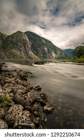 Stream from the Eidfjordvatnet lake flowing to the fjord, mountains of Hardangervidda in the background, Eidfjord, Norway