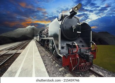 stream engine locomotive train on railways track with beautiful dusky sky and mountain scene