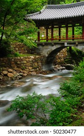 A stream flowing beneath a bridge built using traditional Korean Buddhist architecture - Extended exposure.