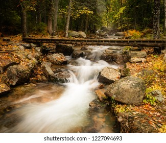 A stream flowing fast with rain water with a foot bridge spanning the expanse..