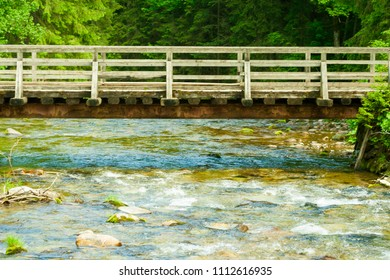 A stream flowing in the mountains and an old wooden bridge over it. A beautiful landscape with a river.